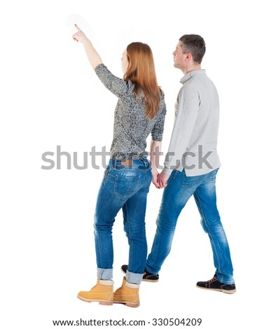 Back view of walking young couple (man and woman) pointing. Rear view people collection. backside view of person. Isolated over white background// She leads by the hand Man and points forward. - stock photo