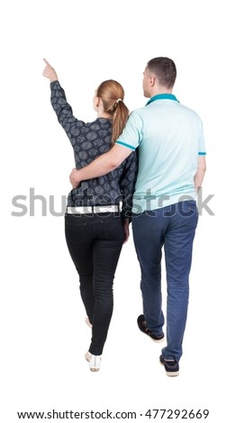 Back view of walking young couple (man and woman) pointing. Rear view people collection. backside view of person. Isolated over white background
