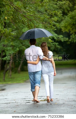 Back view of woman and man walking under umbrella during rain - stock photo