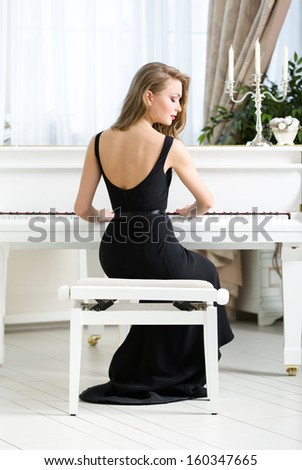 Back view of woman in black dress sitting and playing piano. Concept of music and leisure - stock photo