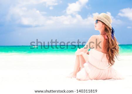 back view of woman in straw hat and dress on tropical beach