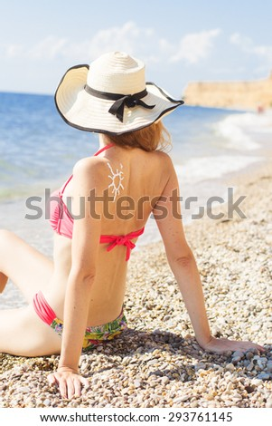 Back view of woman is having sunbathes wearing hat is sitting on the sea cost with sun tan lotion sun drawing  - stock photo