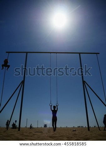 Back view of woman on beach holding gymnastic rings - stock photo
