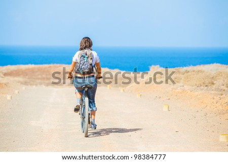 Back view of woman on bike outdoors smiling. - stock photo