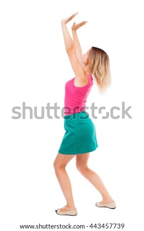 back view of woman  protects hands from what is falling from above. woMan holding heavy load Isolated over white background. Blond girl in green skirt standing sideways and holding the object overhead