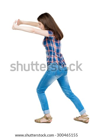 back view of woman pushes wall. Isolated over white background. Rear view people collection.  A young girl in a checkered blue with red stripes leaning trying to move something in the law. - stock photo