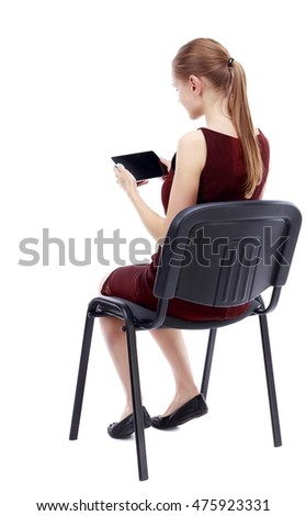 back view of woman sitting on chair and looks at the screen of the tablet. Isolated over white background. A girl in a burgundy dress sitting on a chair and reading a tablet.