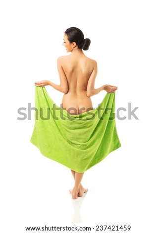 Back view of woman standing wrapped in green towel - stock photo