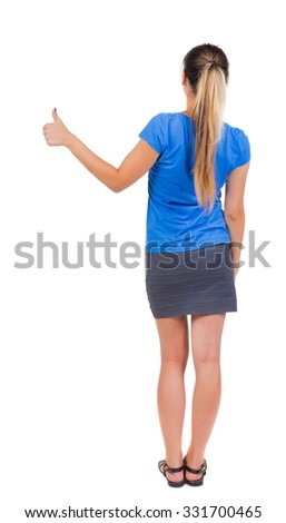 Back view of  woman thumbs up. Rear view people collection. backside view of person. Isolated over white background. Girl in a gray skirt and blue T-shirt shows the right hand thumb up. - stock photo
