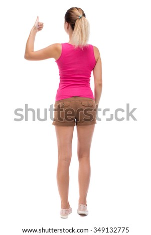 Back view of  woman thumbs up. Rear view people collection. backside view of person. Isolated over white background. Blonde in brown shorts showing a thumbs up with his left hand. - stock photo