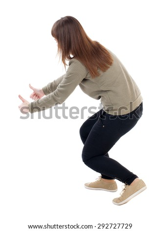 Back view of  woman thumbs up. Rear view people collection. backside view of person. slender blonde in a jeans shows the symbol of success or hitchhiking. To the bottom of the girl showing a thumbs up - stock photo