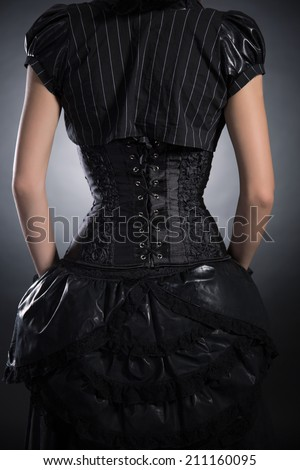 Back view of woman wearing black rose corset and Victorian style outfit, studio shot  - stock photo