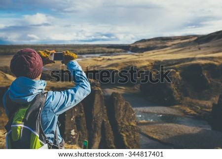Back view of woman wearing winter clothes taking pictures of canyon in Iceland. - stock photo