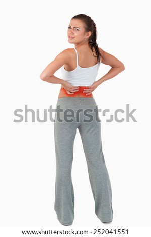 Back view of woman with backache against a white background - stock photo