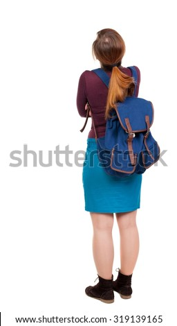 Back view of  woman with backpack looking up. Standing young girl. Rear view people collection.   girl in a blue skirt and a burgundy sweater with a blue backpack standing arms folded looking up. - stock photo