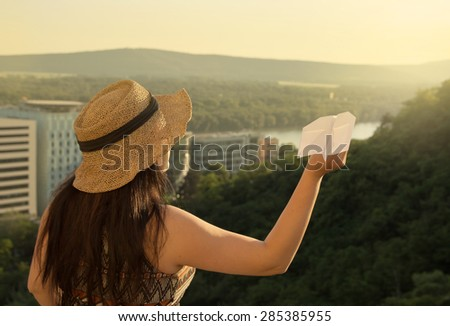 Back View of Woman with Hat and Paper Airplane on Balcony