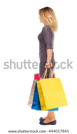 back view of woman with shopping bags . beautiful brunette girl in motion.  backside view of person. Girl in purple dress is standing sideways and holding shopping bags. - stock photo