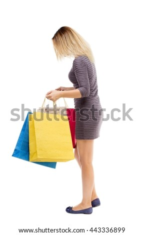 back view of woman with shopping bags. beautiful brunette girl in motion. backside view person. Rear view people collection. Isolated over white background. Girl in dress looking into shopping bags - stock photo