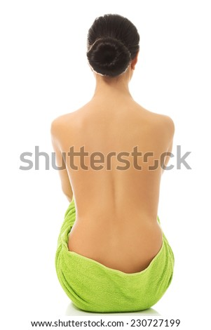 Back view of woman wrapped in green towel - stock photo