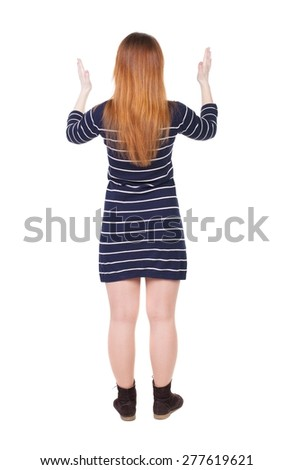 back view of woman. Young woman in vest presses down on something. Isolated over white background. Rear view people collection. backside view of person. She spread her arms out. - stock photo