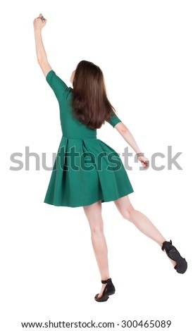 back view of writing beautiful woman. Young girl in dress. Rear view people collection.  backside view of person. The girl in stylish green dress standing on tiptoes writes a felt-tip pen on top.  - stock photo