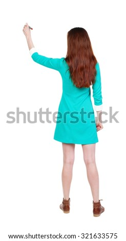 back view of writing beautiful woman. Young girl in dress. Rear view people collection.  backside view of person. Isolated over white background. Girl in dress and leather shoes draws on the wall - stock photo