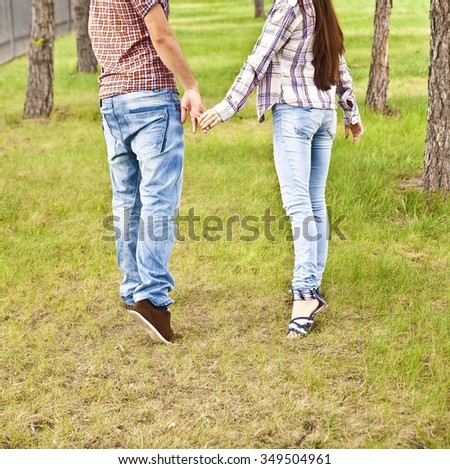 back view of young adult couple holding hands and walking in summer park on fresh green grass along trees in perspective. full length. Blue jeans and shirts. no face - stock photo