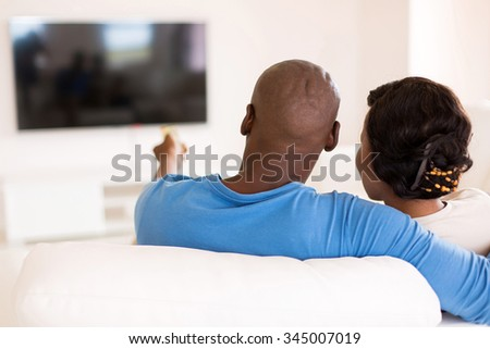 back view of young african couple watching tv in the living room at home - stock photo