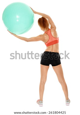 Back view of young athletic woman stretching with a ball, isolated over white background