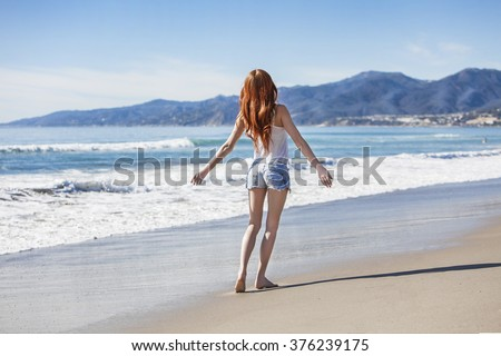 back view of young attractive woman in shorts and shirt playing on beach with sea in front in relax and freedom concept