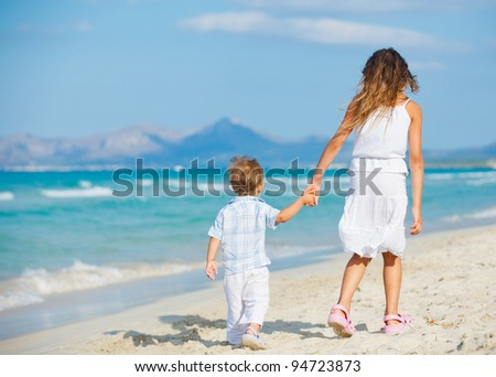 Back view of young beautiful girl and her brather walking at pretty beach. Majorca, Spaine - stock photo