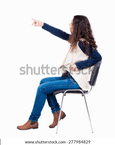 back view of young beautiful  woman sitting on chair and pointing.  girl  watching. Rear view people collection.  backside view of person.  Isolated over white background. - stock photo