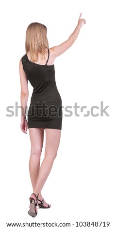 Back view of young blonde woman pointing at wall .beautiful girl in black dress showing gesture. backside view of person. Rear view people collection. Isolated over white background - stock photo