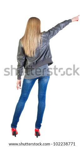 Back view of young blonde woman pointing at wall . beautiful girl in jeans showing gesture. Rear view people collection.  backside view of person.  Isolated over white background.