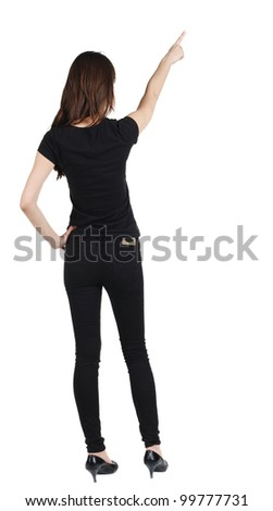 Back view of young brunette woman pointing at wall . beautiful girl in black jeans showing gesture. Rear view. Isolated over white background. - stock photo
