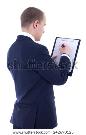 back view of young businessman in suit writing something in clipboard isolated on white background - stock photo
