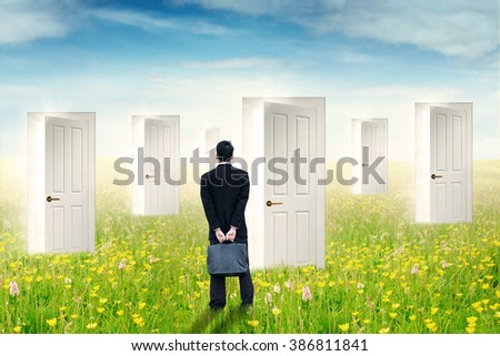 Back view of young businessman standing on the meadow while looking at the open doors to choose the right door - stock photo