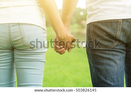 Back view of young casual couple holding hands while walking in the park - dating, love and romance concepts