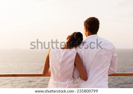 back view of young couple enjoying sunset on cruise - stock photo