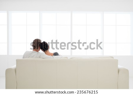 back view of young couple in love relaxing on sofa