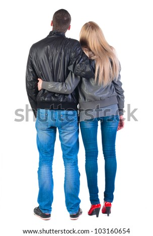 Back view of young couple (man and woman) hug and look into the distance. beautiful friendly girl and guy in jacket and jeans together. Rear view. Isolated over white background.