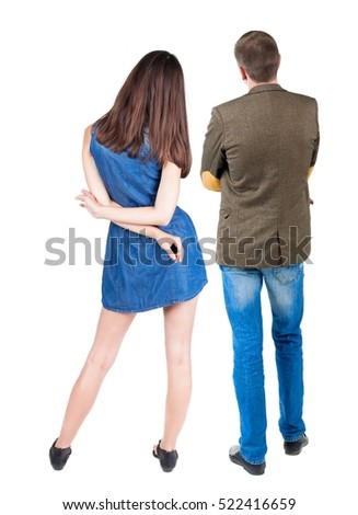 Back view of young couple man and woman hug and look into the distance.  Rear view. Isolated over white background. young woman holds the hand of her husband looking away