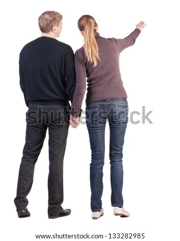 Back view of young couple (man and woman) hug and pointing. beautiful friendly girl and guy together. Rear view. Isolated over white background. wife says to her husband that the important - stock photo