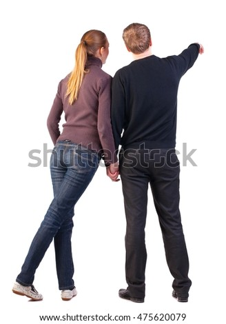 Back view of young couple (man and woman) hug and pointing. beautiful friendly girl and guy together. Rear view. Isolated over white background. warmly dressed couple shows something in the distance