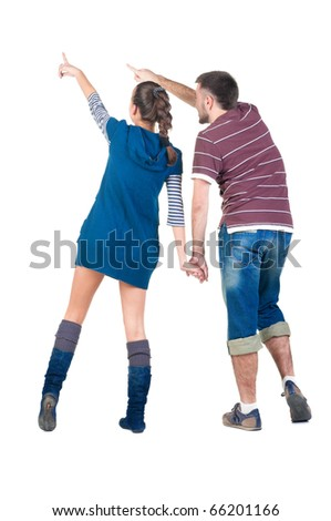 Back view of young couple pointing at white wall . Rear view . - stock photo