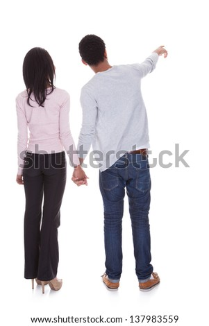 Back View Of Young Couple Pointing Over White Background