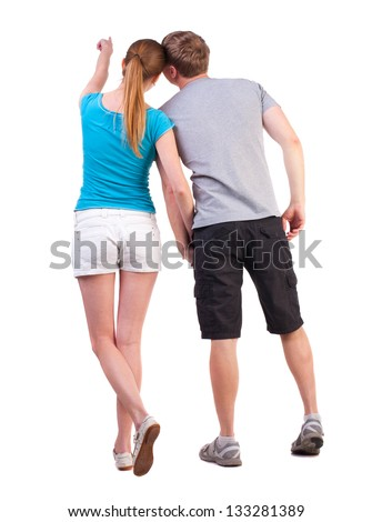 Back view of young couple pointing. Rear view people collection. backside view person.  Isolated over white background. blonde teen shows her boyfriend at something in the distance, holding his hand - stock photo