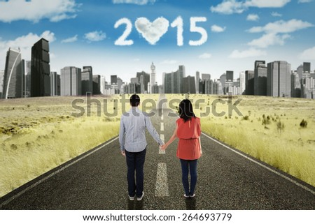 Back view of young couple standing on the road while holding hands and looking at cloud shaped numbers 2015 - stock photo