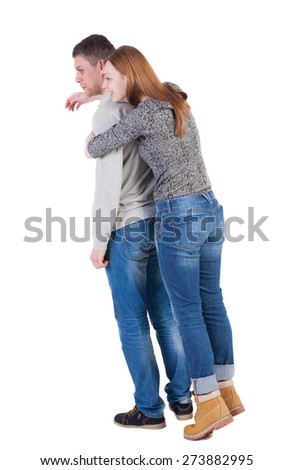 Back view of young embracing couple hug and look into distance. beautiful friendly girl and guy together. Rear view people collection. backside view of person. Laughing girl hugging guy from behind. - stock photo