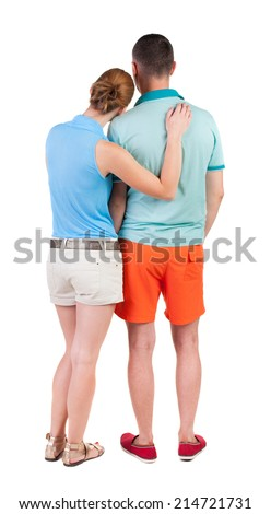 Back view of young embracing couple in shorts  hug and look. friendly girl and guy together. Rear view people collection. backside view of person.  Isolated over white background. - stock photo